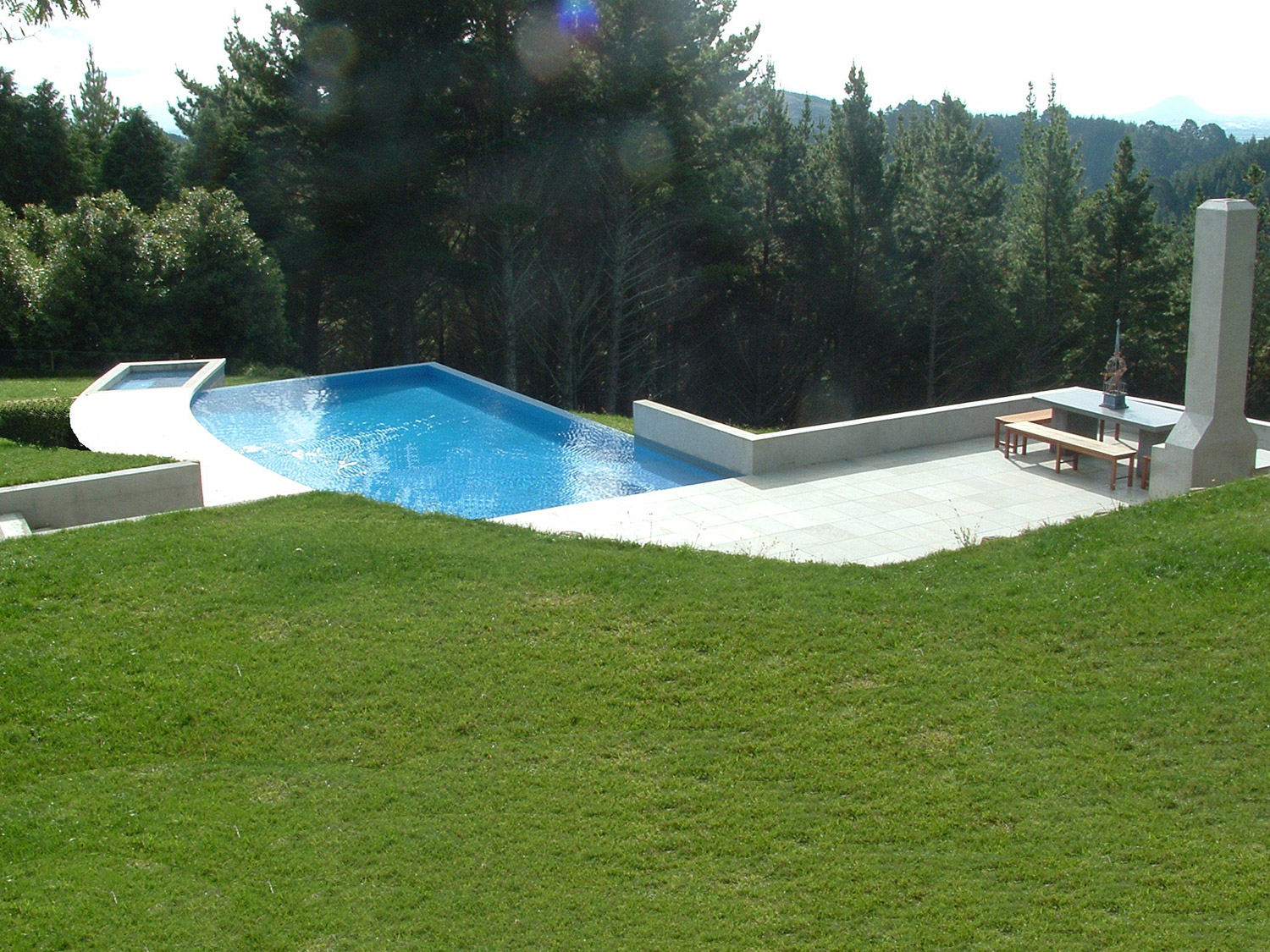 Wet edge swimming pool spa design on sloping site for Pool design company elwira kowalska